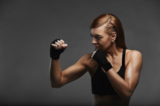 Vrouwelijke bokser met handen in zwarte bokserverbanden in de houding van een bokser op een donkergrijs oppervlak, poseren met een roep om bescherming