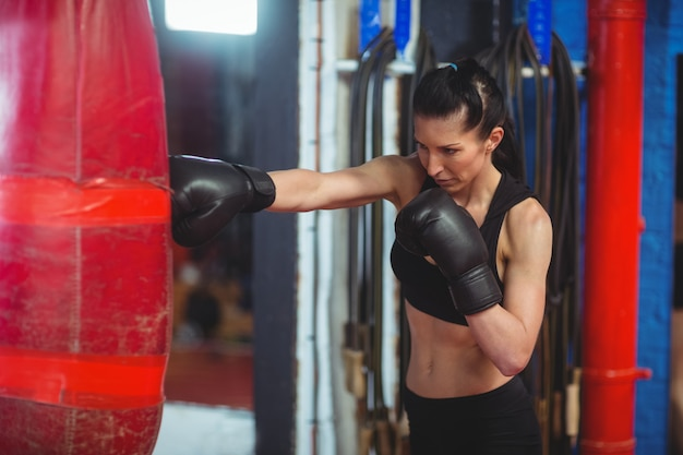 Vrouwelijke bokser oefenen boksen met bokszak