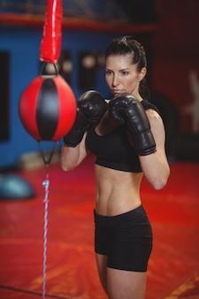 Vrouwelijke bokser oefenen boksen met snelheid boksen bal