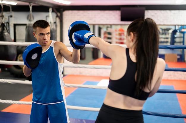 Vrouwelijke bokser oefenen met trainer