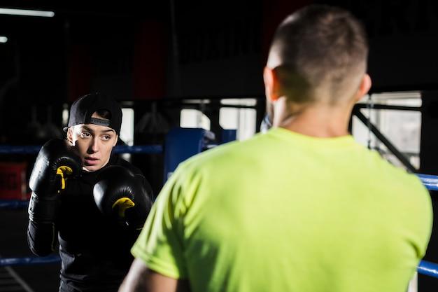 Vrouwelijke bokser training met mannelijke bokser in de ring