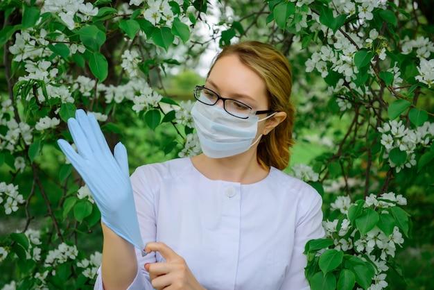 Vrouwelijke botanicus in medische masker en bril zet handschoenen aan, werkt met planten in de botanische tuin