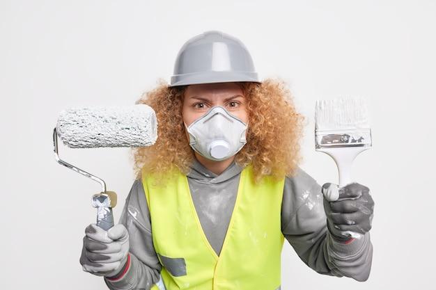 Vrouwelijke bouwer die betrokken is bij het verbouwen van huizen houdt kwast en roller vast en draagt een beschermende helm en gezichtsmasker als professionele aannemer