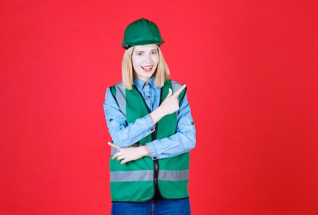 Vrouwelijke bouwer in uniform, helm en wijzende vingers in de rechter- en linkerbovenhoek, met promo-aanbieding met blij gezicht