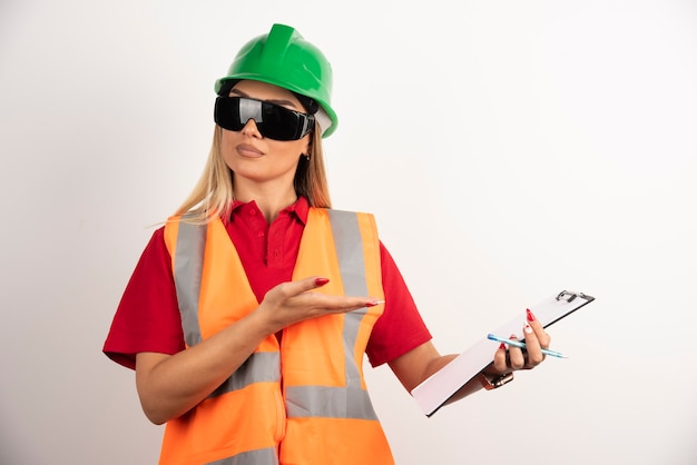 Vrouwelijke bouwer met beschermende brillen die op klembord tonen.