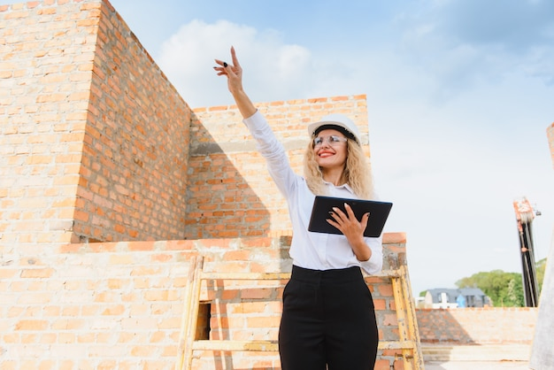 Vrouwelijke bouwingenieur. architect met een tabletcomputer op een bouwplaats