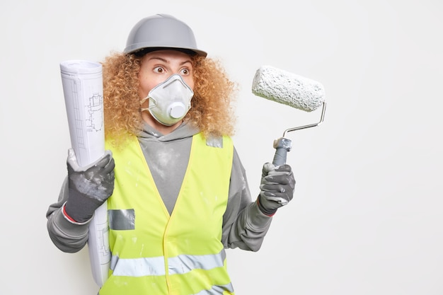 Vrouwelijke bouwingenieur houdt architecturaal project en verfroller vast