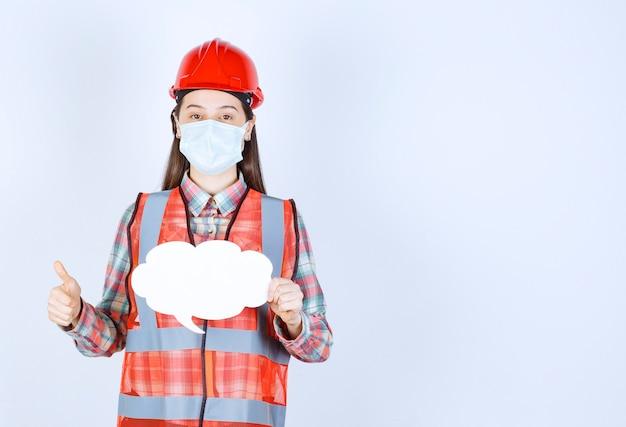 Vrouwelijke bouwingenieur in veiligheidsmasker en rode helm die een infobord in de vorm van een wolk vasthoudt en een positief handteken toont