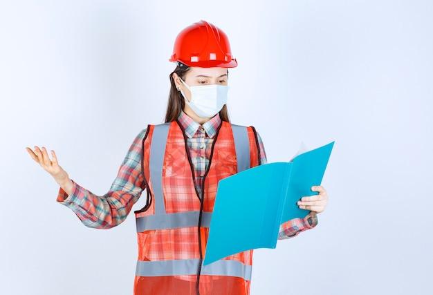 Vrouwelijke bouwingenieur in veiligheidsmasker en rode helm met een blauwe map en ziet er verward en attent uit.