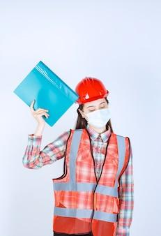 Vrouwelijke bouwingenieur met veiligheidsmasker en rode helm die een blauwe map vasthoudt en er verward en attent uitziet