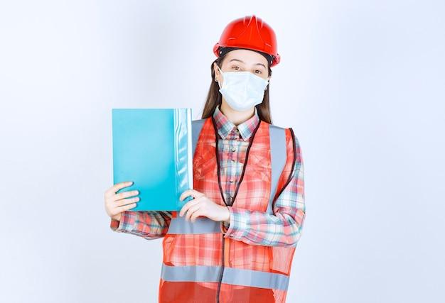 Vrouwelijke bouwingenieur met veiligheidsmasker en rode helm die een blauwe map vasthoudt en ter verificatie presenteert