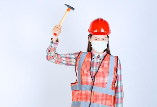 Vrouwelijke bouwingenieur met veiligheidsmasker en rode helm die een houten bijl vasthoudt, deze opheft en zich klaarmaakt om te slaan