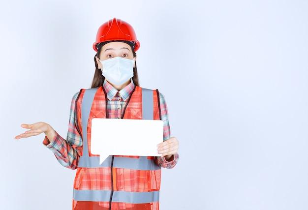 Vrouwelijke bouwingenieur met veiligheidsmasker en rode helm die een rechthoekig leeg infobord vasthoudt en er verward en attent uitziet
