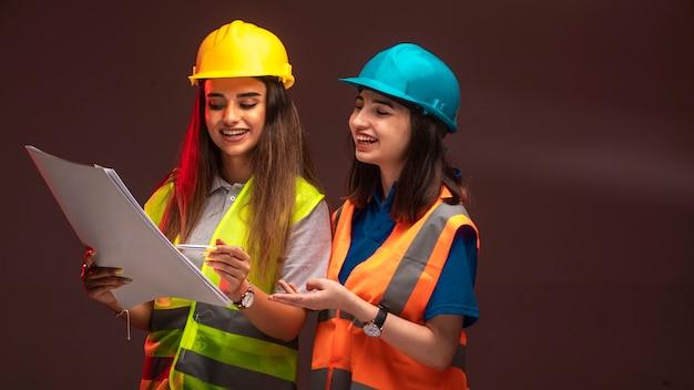 Vrouwelijke bouwingenieurs die samenwerken en het projectplan bespreken.