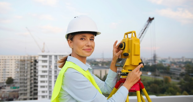 Vrouwelijke bouwmanager en ingenieur die beschermende helm met ingenieurapparatuur draagt die op de bouwplaats werkt.