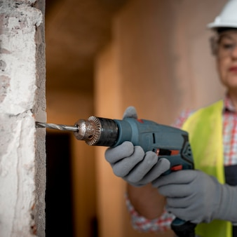 Vrouwelijke bouwvakker met helm en elektrische boor