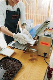 Vrouwelijke branderarbeider in schort en rubberen handschoenen naden van koffiepakketten afdichten
