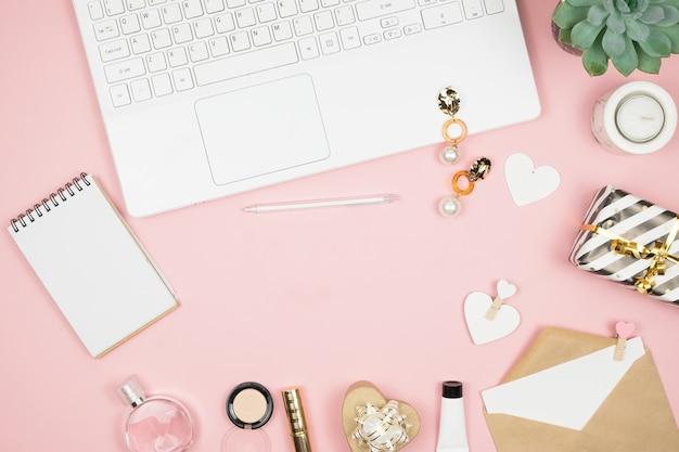 Vrouwelijke bureaudesktop met kantooraccessoires op roze oppervlak. dameswerkruimte met vetplanten, kaarsen en cosmetica.