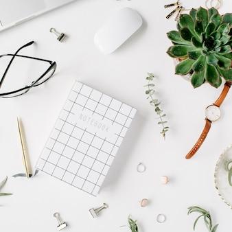 Vrouwelijke bureauwerkruimte met laptop, sappig dagboek, bril, horloge op witte achtergrond.