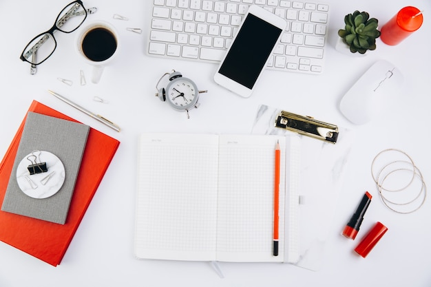Vrouwelijke bureauwerkruimte met succulent, glazen, toetsenbord en notitieboekje op wit