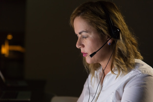 Vrouwelijke call centreexploitant in donker bureau
