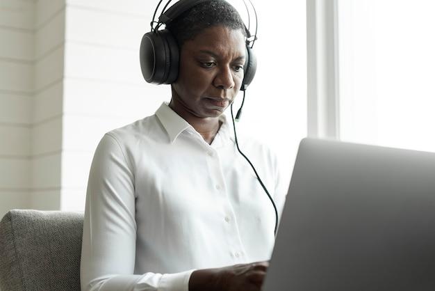 Vrouwelijke callcentermedewerker die een laptop gebruikt