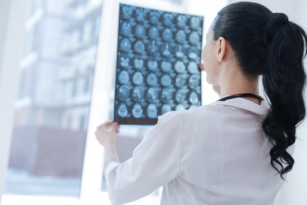 Vrouwelijke charmante slimme oncoloog die in de kliniek werkt tijdens het onderzoeken van het beeld van de röntgenfoto van de hersenen en het uiten van positiviteit