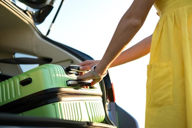 Vrouwelijke chauffeur in zomerjurk die groene koffer in haar kofferbak stopt. reizen en vakanties concept.