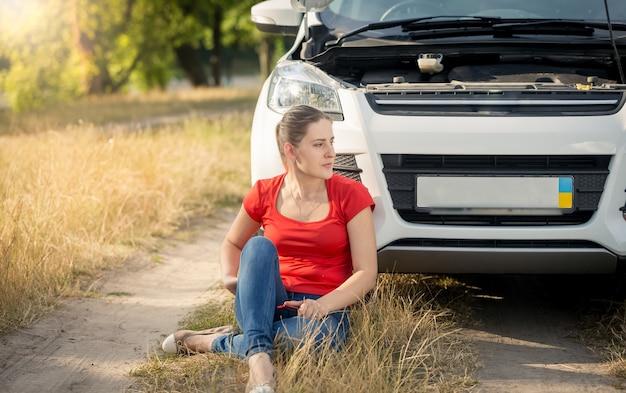 Vrouwelijke chauffeur zit op de grond naast een kapotte auto en roept om hulp