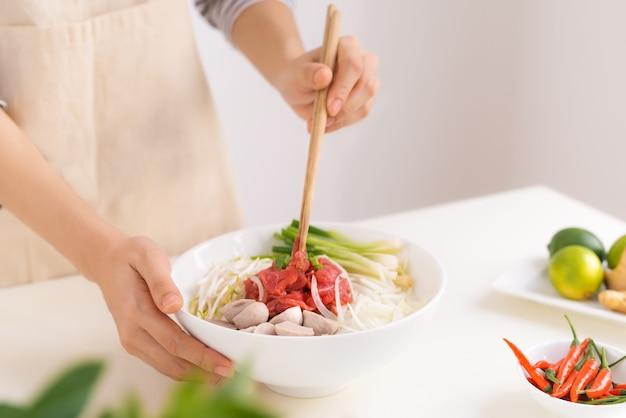 Vrouwelijke chef-kok bereidt traditionele vietnamese soep pho bo met kruiden, vlees, rijstnoedels