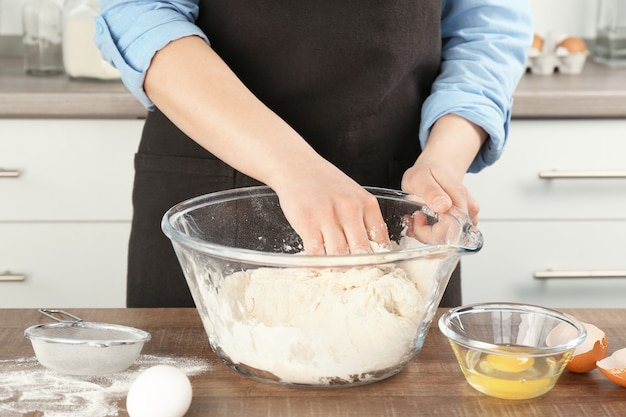 Vrouwelijke chef-kok die deeg in keuken maakt
