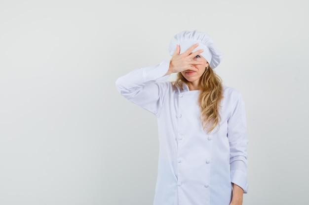 Vrouwelijke chef-kok die door vingers in wit uniform kijkt en beschaamd kijkt
