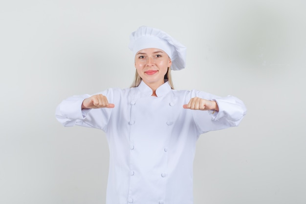 Vrouwelijke chef-kok die duimen richt naar zichzelf in wit uniform en vrolijk kijkt.