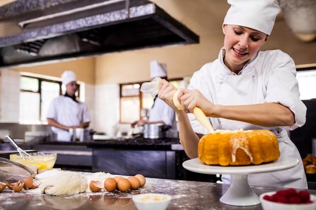 Vrouwelijke chef-kok die een cake in keuken leidingen