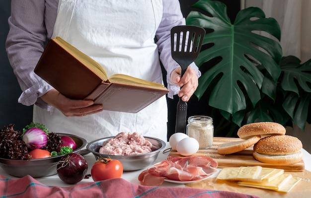 Vrouwelijke chef-kok die grote hamburger of cheeseburger kookt en op zoek is naar een leerboek met kookrecept-zelfstudie.
