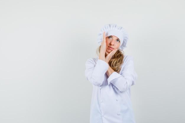 Vrouwelijke chef-kok die haar gezichtshuid controleert terwijl hij in wit uniform opzoekt en er schattig uitziet.
