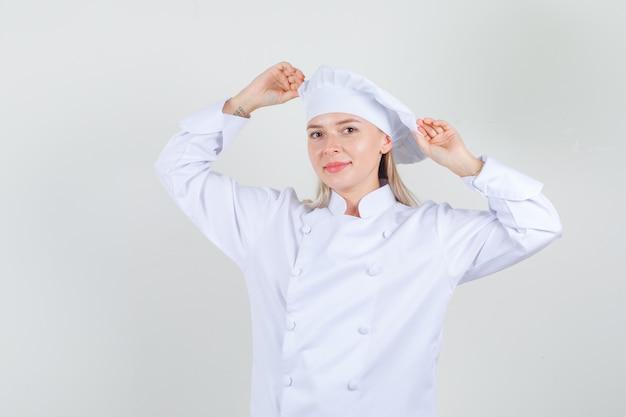 Vrouwelijke chef-kok die haar hoed in wit uniform houdt en vrolijk kijkt