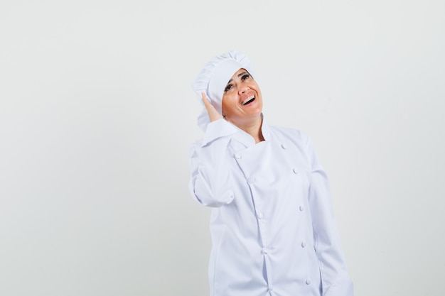 Vrouwelijke chef-kok die hand dichtbij oor in wit uniform houdt en vrolijk kijkt