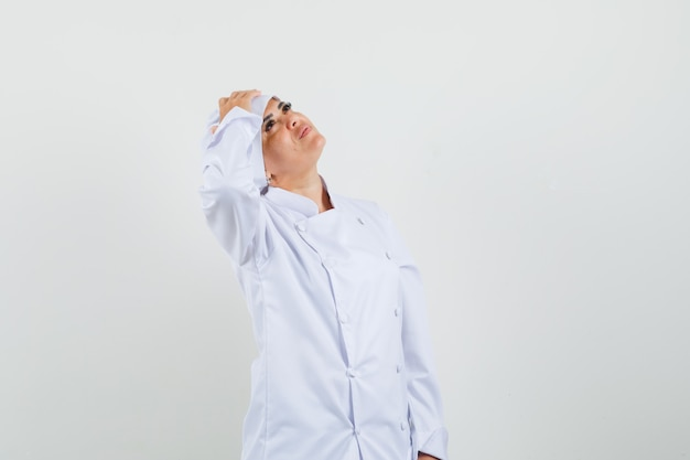 Vrouwelijke chef-kok die hand op voorhoofd in wit uniform houdt en dromerig kijkt