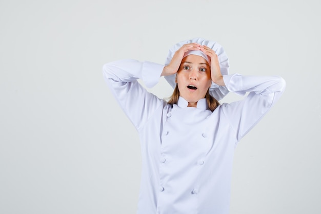 Vrouwelijke chef-kok die handen op hoofd in wit uniform houdt en verbaasd kijkt
