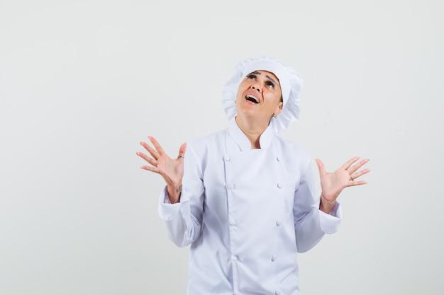 Vrouwelijke chef-kok die handen opheft, in wit uniform kijkt en opgewonden kijkt