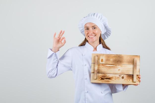Vrouwelijke chef-kok die houten dienblad met ok teken in wit uniform houdt en vrolijk kijkt