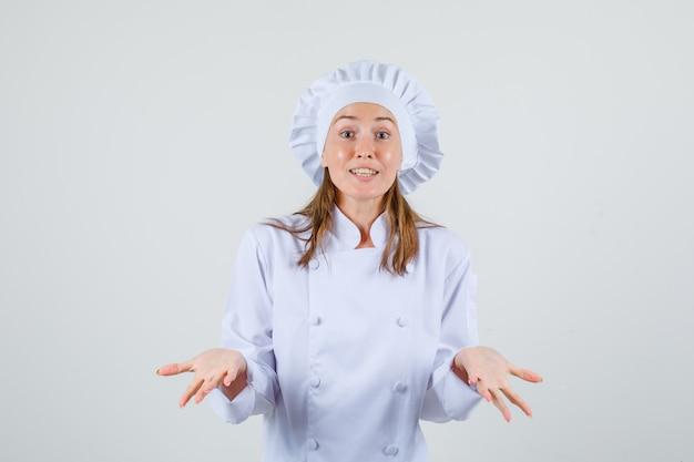 Vrouwelijke chef-kok die hulpeloos gebaar in wit uniform toont en verward kijkt