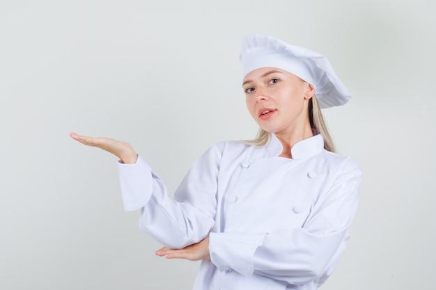 Vrouwelijke chef-kok die iets in wit uniform welkom heet of toont en vrolijk kijkt
