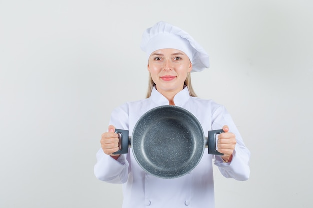 Vrouwelijke chef-kok die lege pan in wit uniform houdt en vrolijk kijkt.