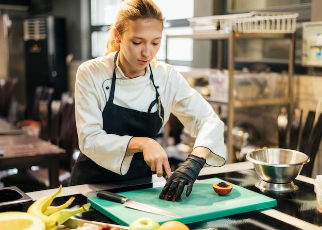 Vrouwelijke chef-kok die met handschoenen fruit in de keuken snijden