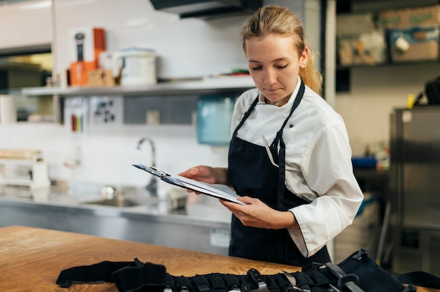 Vrouwelijke chef-kok die met klembord haar hulpmiddelen controleert