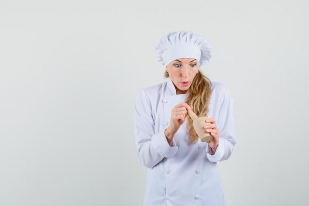 Vrouwelijke chef-kok die mortel in wit uniform onderzoekt en verbaasd kijkt.
