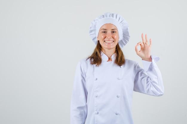 Vrouwelijke chef-kok die ok gebaar in wit uniform toont en blij kijkt. vooraanzicht.