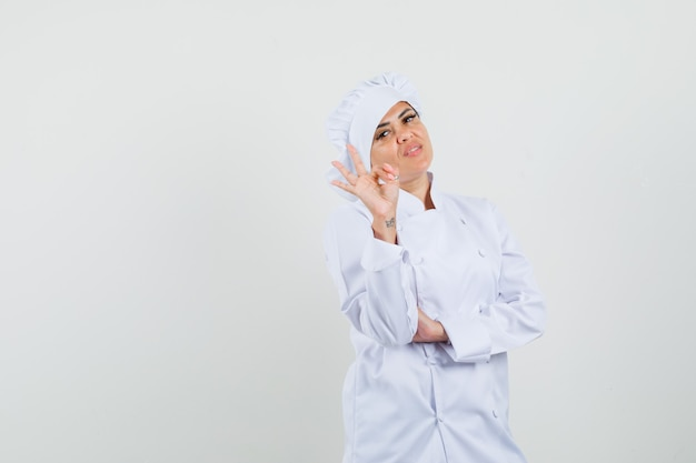 Vrouwelijke chef-kok die ok gebaar in wit uniform toont en zelfverzekerd kijkt